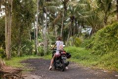巴厘岛,印度尼西亚- 2017年11月25日:一辆摩托车的年轻愉快的妇女在热带巴厘岛的密林雨林 库存照片