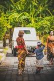 巴厘岛,印度尼西亚- 2018年4月13日:与欧洲少妇的亚洲孩子在巴厘语婚礼之日 印度尼西亚孩子 库存图片