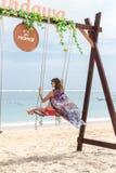 巴厘岛,印度尼西亚- 2017年10月8日:在摇摆的美好的年轻女性开会在海岸 可视巴厘岛美丽的印度尼西亚海岛kuta人连续形状日落的城镇 图库摄影