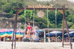 巴厘岛,印度尼西亚- 2017年10月8日:在摇摆的美好的年轻女性开会在海岸 可视巴厘岛美丽的印度尼西亚海岛kuta人连续形状日落的城镇 库存照片