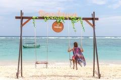 巴厘岛,印度尼西亚- 2017年10月8日:在摇摆的美好的年轻女性开会在海岸 可视巴厘岛美丽的印度尼西亚海岛kuta人连续形状日落的城镇 库存图片