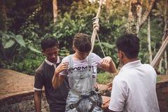 巴厘岛,印度尼西亚- 2017年11月25日:在摇摆被冲击的少妇在峭壁以后 可视巴厘岛美丽的印度尼西亚海岛kuta人连续形状日落的城镇 免版税图库摄影