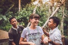 巴厘岛,印度尼西亚- 2017年11月25日:在摇摆被冲击的少妇在峭壁以后 可视巴厘岛美丽的印度尼西亚海岛kuta人连续形状日落的城镇 免版税库存图片