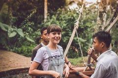 巴厘岛,印度尼西亚- 2017年11月25日:在摇摆被冲击的少妇在峭壁以后 可视巴厘岛美丽的印度尼西亚海岛kuta人连续形状日落的城镇 库存照片