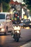 巴厘岛,印度尼西亚- 2017年10月12日:在Legian街道,库塔,巴厘岛,印度尼西亚上的滑行车 摩托车交通 库存图片