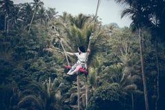 巴厘岛,印度尼西亚- 2017年12月26日:妇女获得乐趣摇摆在密林 摇摆在巴厘岛雨林的妇女  免版税图库摄影