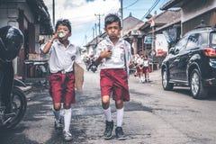巴厘岛,印度尼西亚- 2018年5月23日:小组一个校服的巴厘语男小学生在街道上在村庄 免版税库存照片