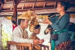 巴厘岛,印度尼西亚- 2018年4月13日:巴厘语婚礼的新婚佳偶 传统婚礼 免版税库存图片