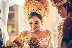 巴厘岛,印度尼西亚- 2018年4月13日:巴厘语婚礼的新婚佳偶 传统婚礼 免版税库存照片