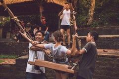 巴厘岛,印度尼西亚- 2017年11月25日:帮助女孩的两个人下来坐在峭壁的摇摆 热带巴厘岛 免版税库存照片
