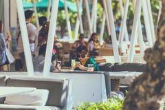 巴厘岛,印度尼西亚- 2017年10月12日:愉快的游人夫妇户外咖啡馆的,巴厘岛 库存照片