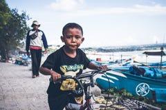巴厘岛,印度尼西亚- 2017年4月12日:自行车的巴厘语男孩 图库摄影
