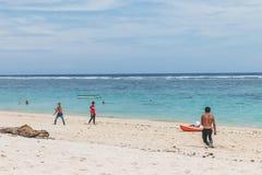 巴厘岛,印度尼西亚- 2017年10月8日:踢橄榄球的朋友在海滩Pandawa,巴厘岛 免版税库存图片