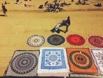 巴塞罗那,西班牙, 2016年11月:在海滩的非法卖主出售地毯 免版税库存图片