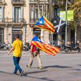 巴塞罗那,西班牙- 2017年10月3日:扛加泰罗尼亚的旗子的示威者在独立的抗议期间在巴塞罗那 图库摄影