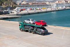 巴塞罗那,西班牙- 2016年3月30日:拖车运载在海港的位子和默西迪丝汽车 汽车出口和进口贸易 库存图片