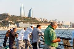 巴库,阿塞拜疆- 2015年7月16日, :里海的渔夫以市巴库为背景 免版税库存照片