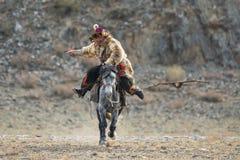 巴彦Ulgii,瓦剌,鹫节日, 2017年10月01日:在狼毛皮传统衣裳的蒙古车手猎人  库存图片