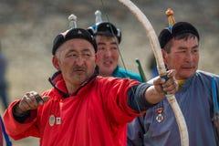 巴彦Ulgii,蒙古- 2017年10月01日:传统鹫节日,射箭竞争 红色长袍的未知的前浆手 库存照片