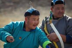 巴彦Ulgii,蒙古- 2017年10月01日:传统鹫节日,射箭竞争 红色长袍的未知的前浆手 免版税库存图片