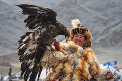 巴彦Ulgii,蒙古- 2017年10月01日:在狐皮传统衣裳的印象深刻的蒙古猎人与一只鹫的在韩 免版税库存照片