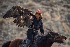 巴彦Ulgii,蒙古- 2017年10月01日:鹫节日 在传统衣裳的印象深刻的蒙古猎人横跨Hors 库存图片