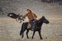 巴彦Ulgii,蒙古- 2017年10月01日:鹫节日 未知的蒙古猎人跨着所谓的Berkutchi在布朗 免版税库存照片