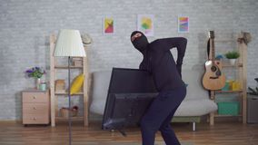 巴拉克拉法帽面具的匿名窃贼窃取电视在房子里和体验背部疼痛伤害的 股票录像