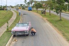 巴拉德罗角,古巴- 2018年1月05日:一个人是变速轮到在路的减速火箭的经典美国汽车到巴拉德罗角在古巴 图库摄影