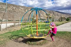 巴拿马草帽的一个小女孩,摇摆在转盘 在美丽的风景和山后 夏天 免版税库存图片