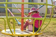 巴拿马草帽的一个小女孩,摇摆在转盘 在美丽的风景和山后 夏天 免版税库存照片