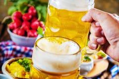 巴法力亚啤酒用软的椒盐脆饼、麦子和蛇麻草在土气木 免版税图库摄影