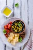 巴马干酪、西红柿、橄榄和杏仁开胃小菜板材  免版税库存图片