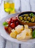 巴马干酪、西红柿、橄榄和杏仁开胃小菜板材  免版税图库摄影
