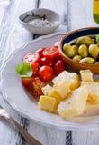 巴马干酪、西红柿、橄榄和杏仁开胃小菜板材  库存照片