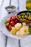 巴马干酪、西红柿、橄榄和杏仁开胃小菜板材  库存图片