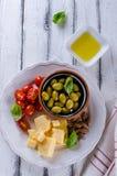 巴马干酪、西红柿、橄榄和杏仁开胃小菜板材  图库摄影