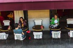 巴黎人在巴黎享受食物和饮料在咖啡馆边路 免版税库存图片