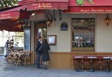 巴黎,法国- 2016年10月16日:学习在著名巴黎人咖啡馆Berthillon的两三名男人和妇女菜单在Notre Da附近 免版税图库摄影