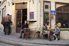 巴黎,法国- 2011年4月11日:愉快的朋友谈话在夏天咖啡馆,都市户外 库存照片