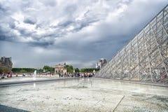巴黎,法国- 2017年6月02日:罗浮宫庭院有玻璃金字塔的和人们在多云天空排队 法国加州地标  免版税库存照片