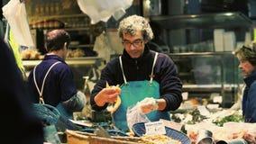 巴黎,法国- 2017年10月7日 人在鱼和海鲜的包装虾失去作用在地方食物市场上 库存图片