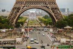 巴黎,法国2017年7月24日:一条路的艾菲尔铁塔特写镜头有汽车和公共汽车交通的从运输者,在曲拱下的段落 图库摄影
