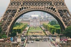 巴黎,法国2017年7月24日:一条路的艾菲尔铁塔特写镜头有汽车和公共汽车交通的从运输者,在曲拱下的段落 库存照片