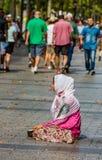 巴黎- 8月10 -一位未认出的女性在爱丽舍的街道上乞求2015年8月10日在巴黎,法国 库存照片