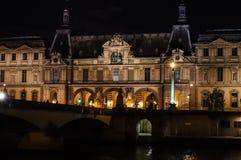 巴黎/法国- 2019年4月03日 罗浮宫巴黎和桥梁Pont在河塞纳河的du Carrousel在晚上 免版税库存图片