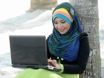 使用膝上型计算机的围巾女孩在海滩 库存照片