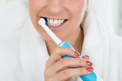 浴巾掠过的牙的妇女有电牙刷的 免版税库存照片