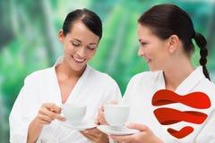 浴巾的喝清凉茶的美丽的朋友的综合图象 库存照片
