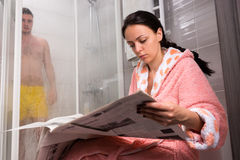 浴巾的女性读报纸和等待她的boyfr的 免版税库存照片